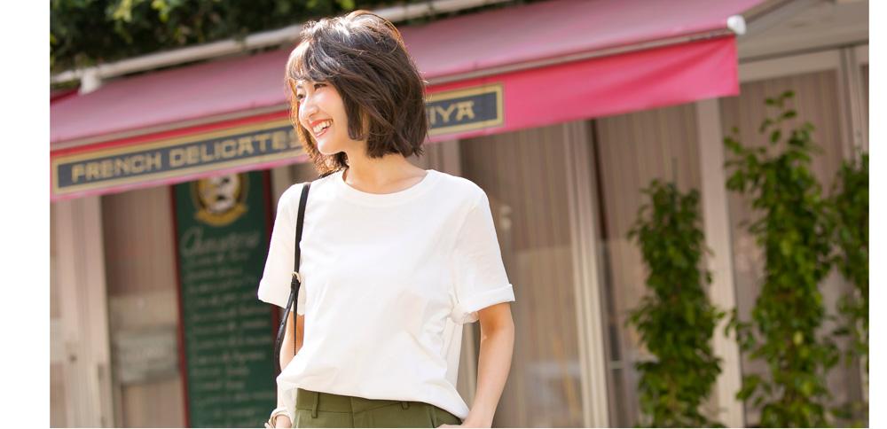 金子麻貴さんがプルオーバーにストレートパンツを合わせたコーデで左を向いて笑顔でポージング