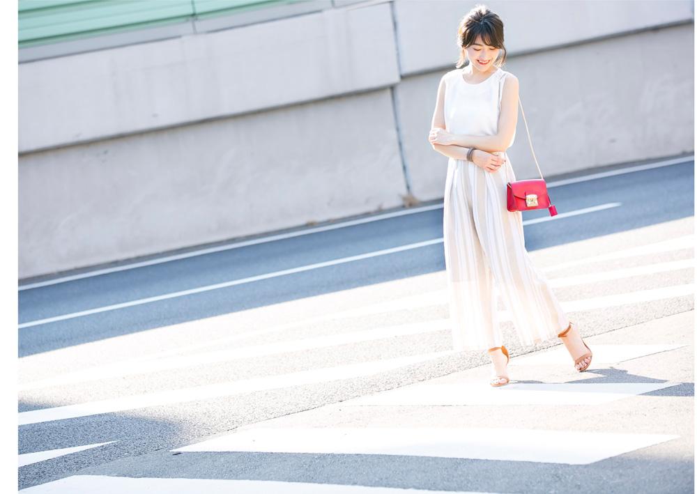 金子麻貴さんがプルオーバーにリネンワイドパンツを合わせたコーデでうつむいて微笑んでいるポージング
