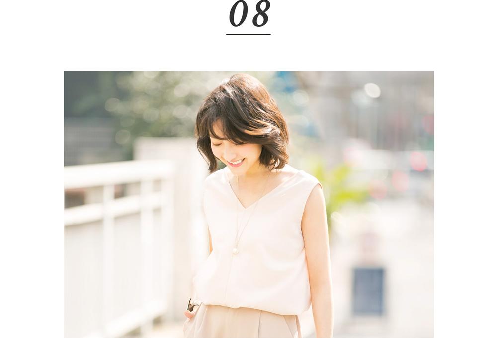 金子麻貴さんがプルオーバーとテーパードパンツでスタイリングしたコーデで俯き微笑んでポージング