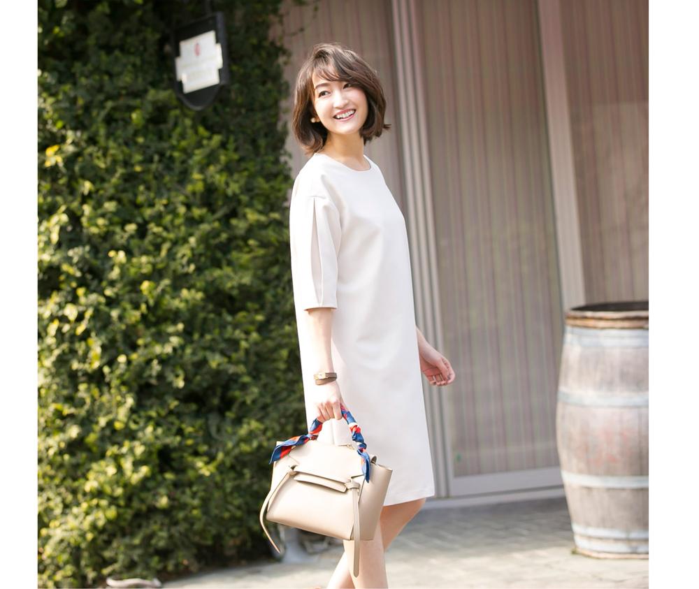 金子麻貴さんがタックスリーブワンピースでスタイリングしたコーデで左を向き笑顔でポージング