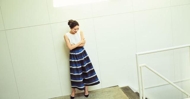 リネンライクなボーダーリボンベルトパンツを穿いて腕を組んでいる大日方久美子さん