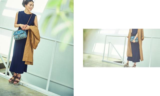 ネイビーのロングスリットIラインマキシワンピースを着て横を向いて微笑んでいる大日方久美子さん