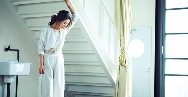 白でまとめたコーディネートにベージュのサッシュベルトを巻いている大日方久美子さん