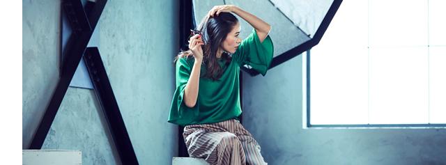 グリーンのトップスとストライプのパンツを着て髪をかき上げている大日方久美子さん