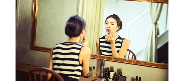 モノトーンのコーディネートに赤リップを塗っている大日方久美子さん