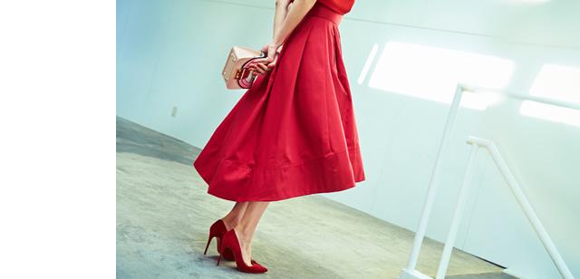 フレアスカートをふわっと広げて立つ大日方久美子さんのパーツアップ